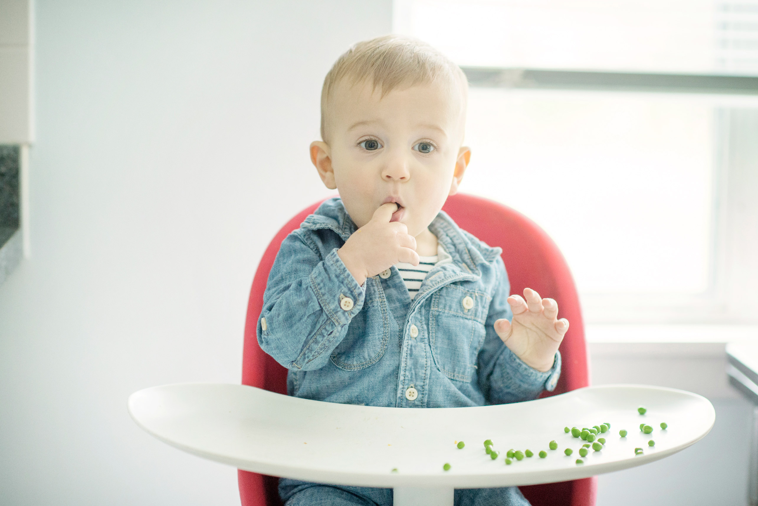 toddler eating peas in high chair