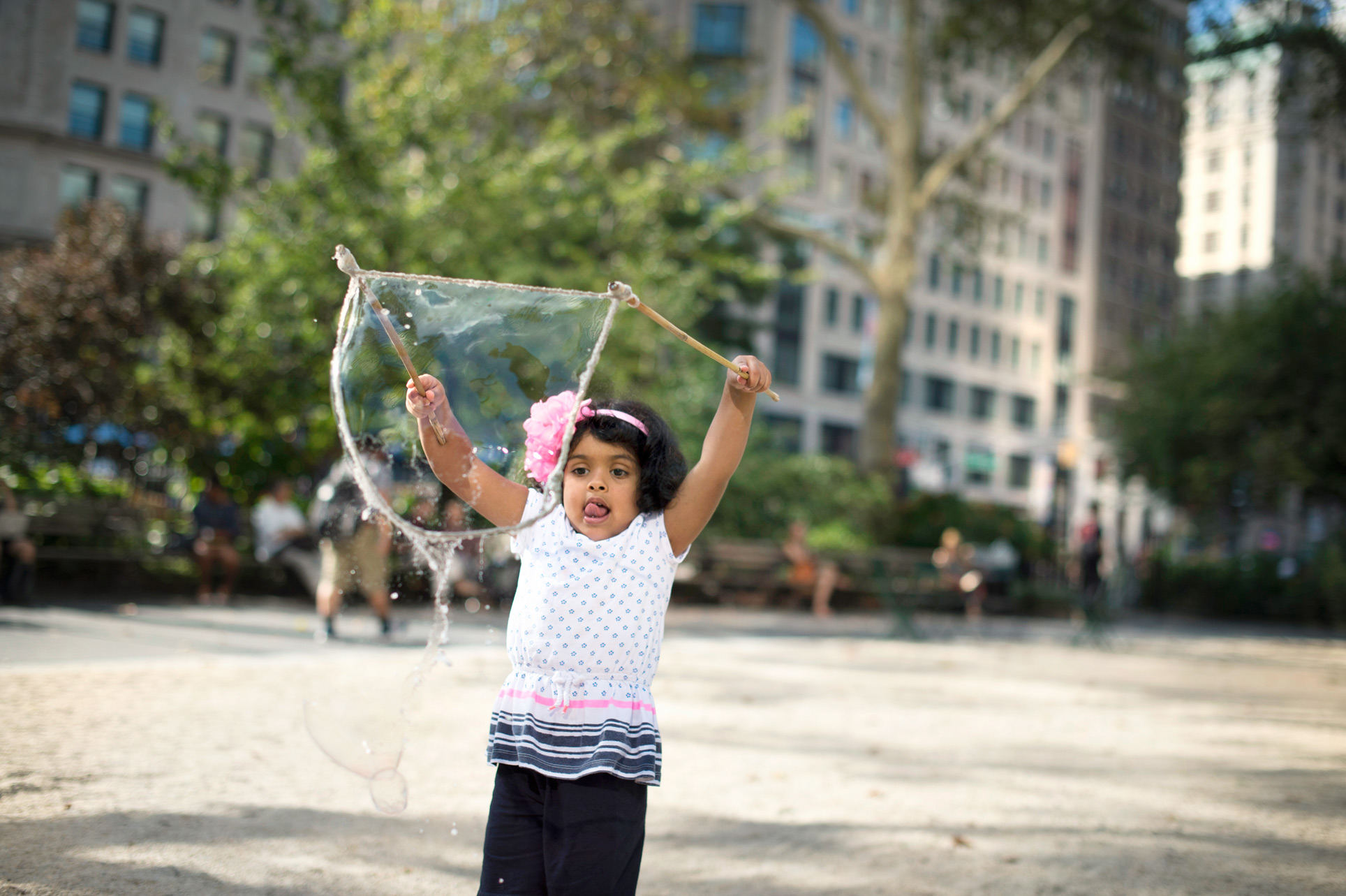 Girl in NYC park playing with giant bubble