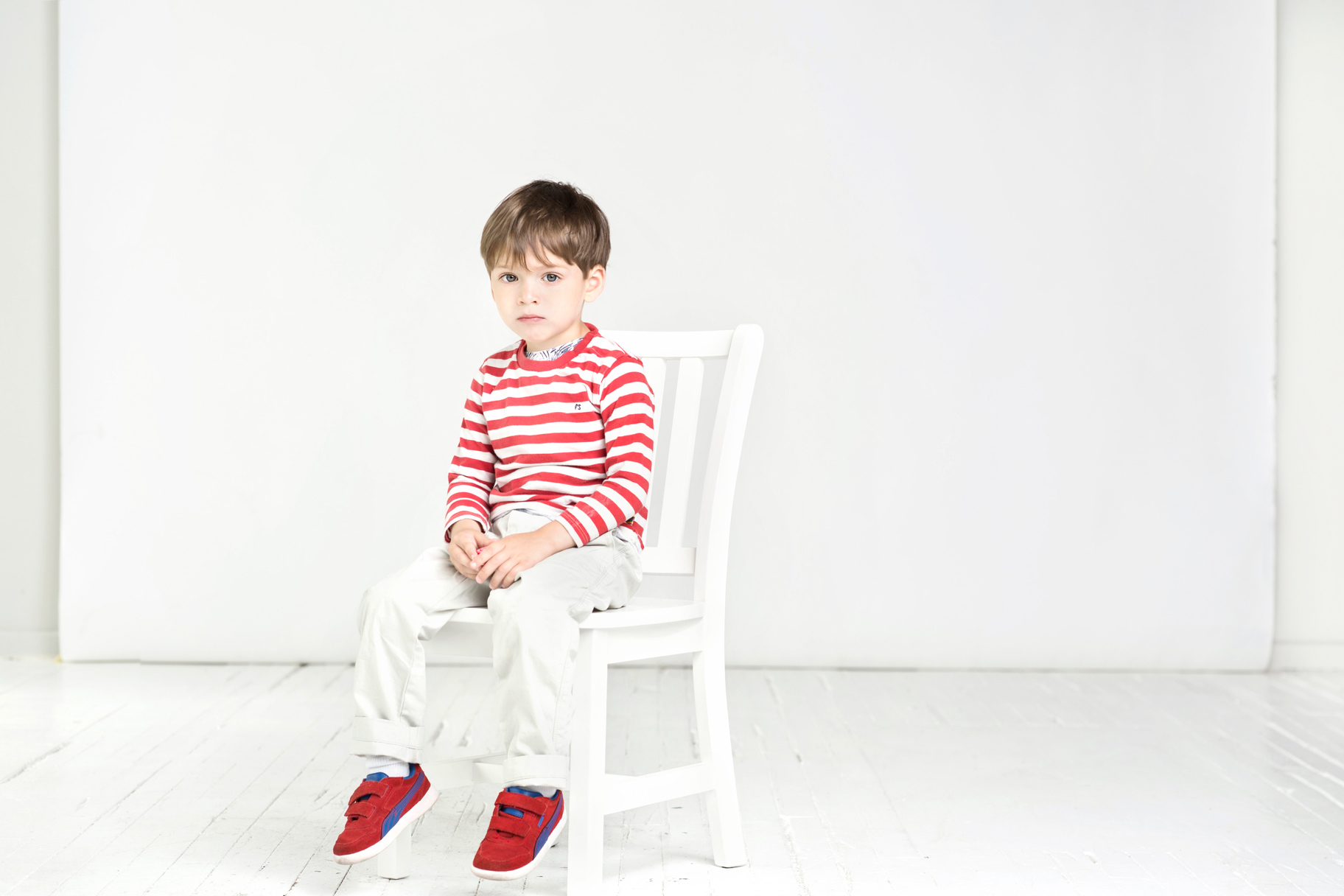 boy sitting on chair on white sweep in studio with red striped shirt
