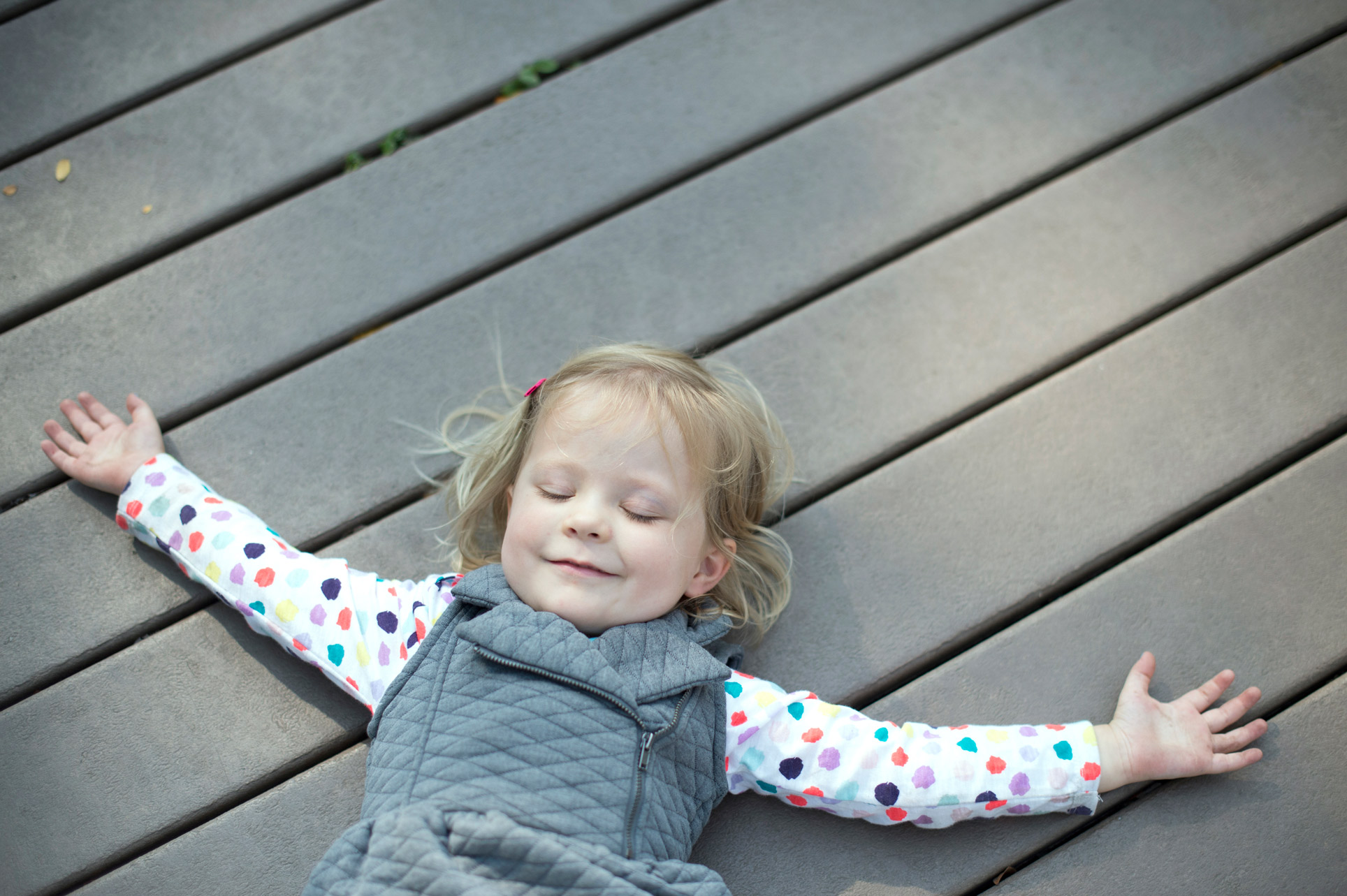 girl lying on ground smiling