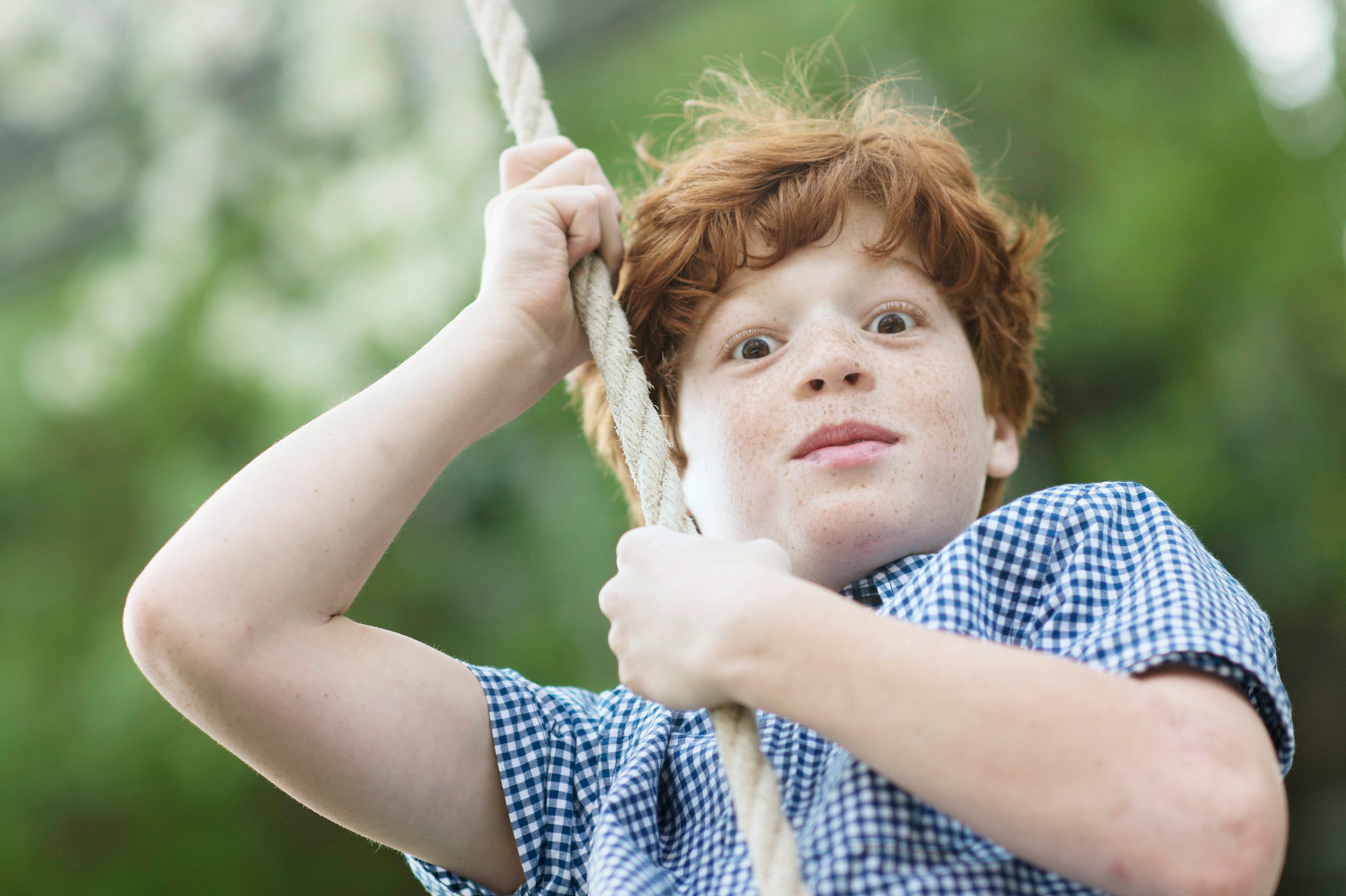 red haired boy on swing
