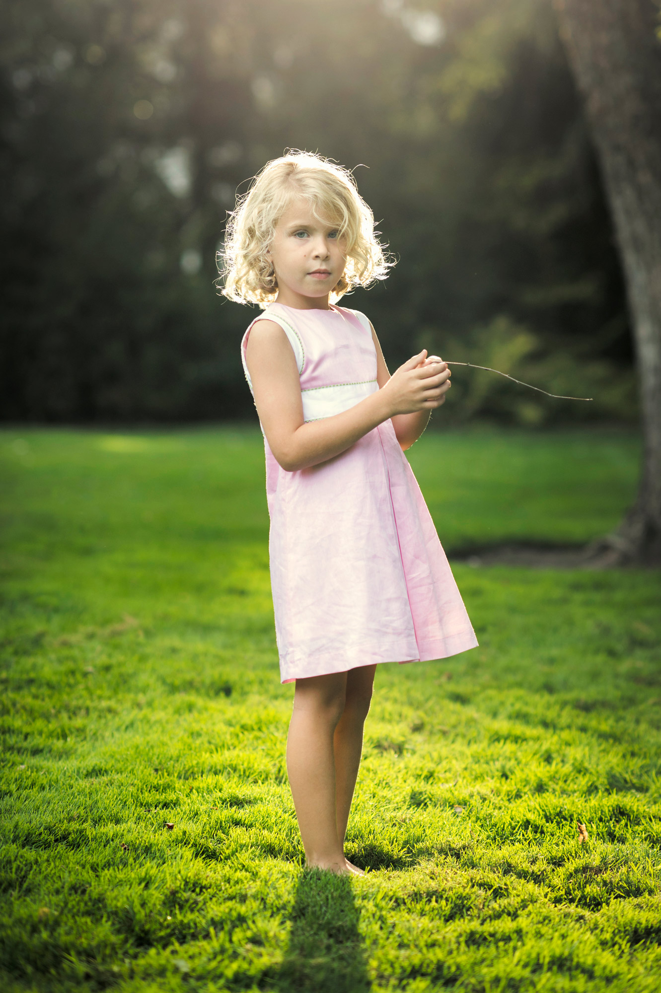 girl in pink dress holding stick