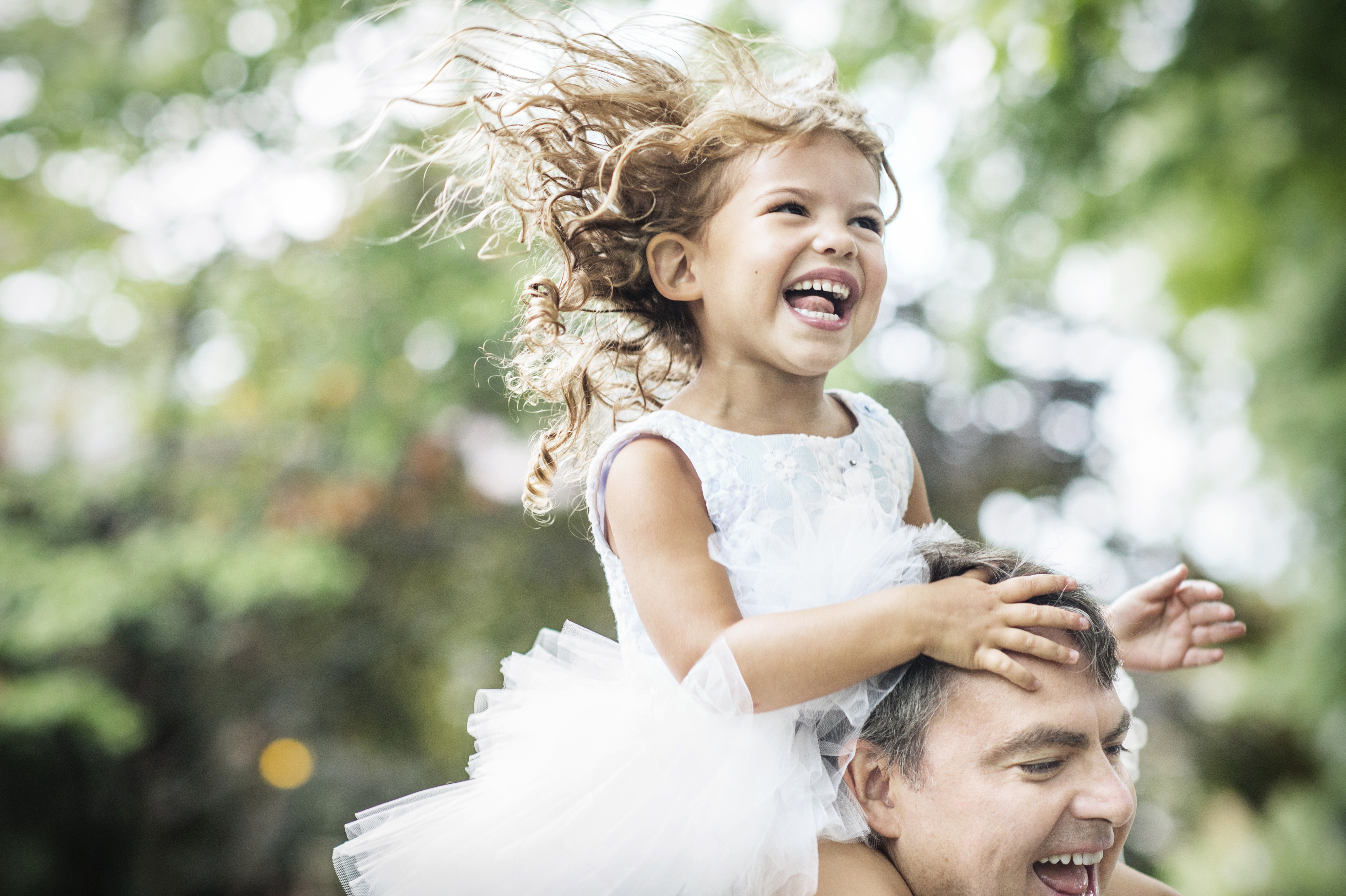 girl laughing on dads shoulders