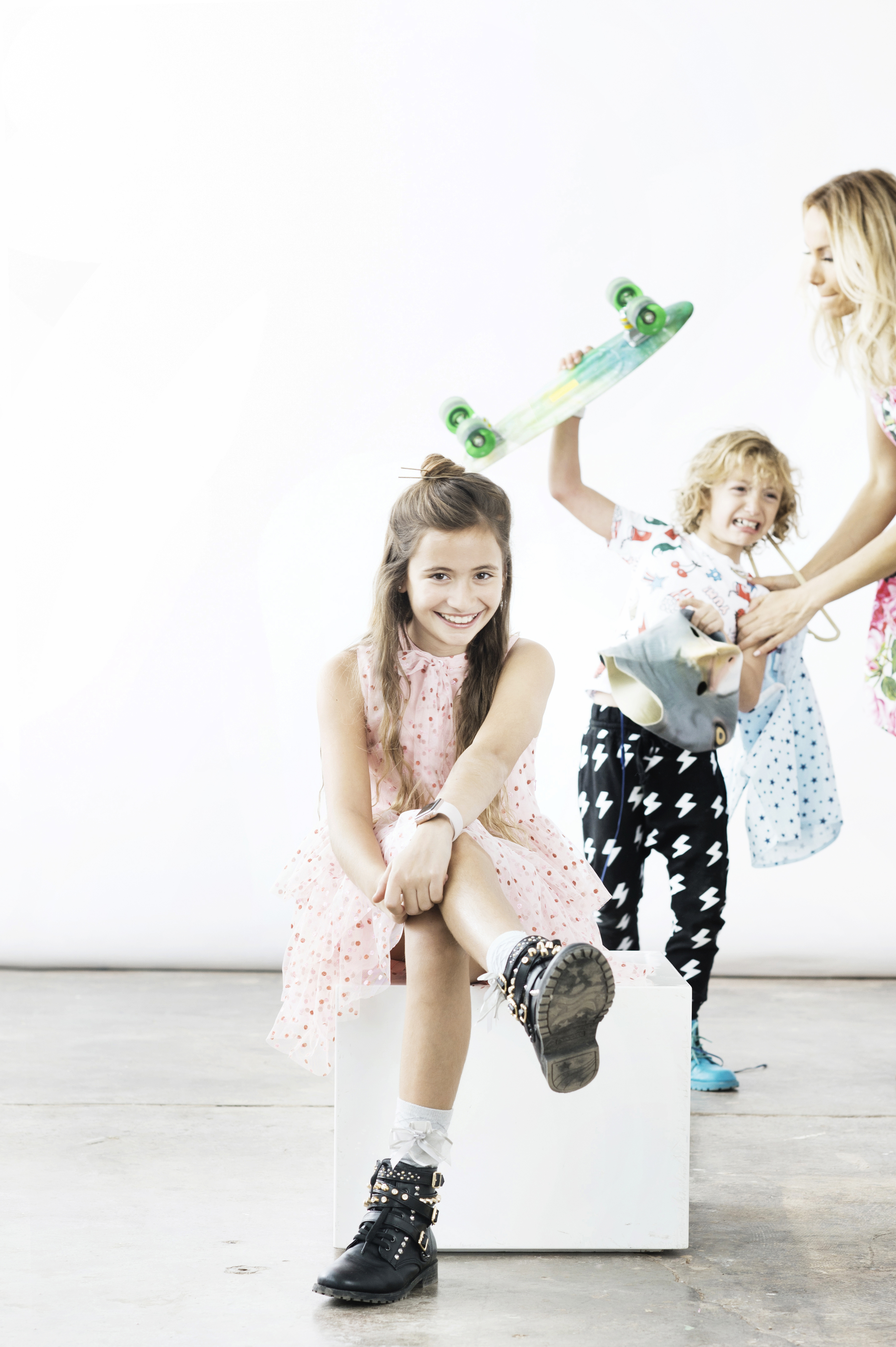 brother with skateboard and sister with mom in studio