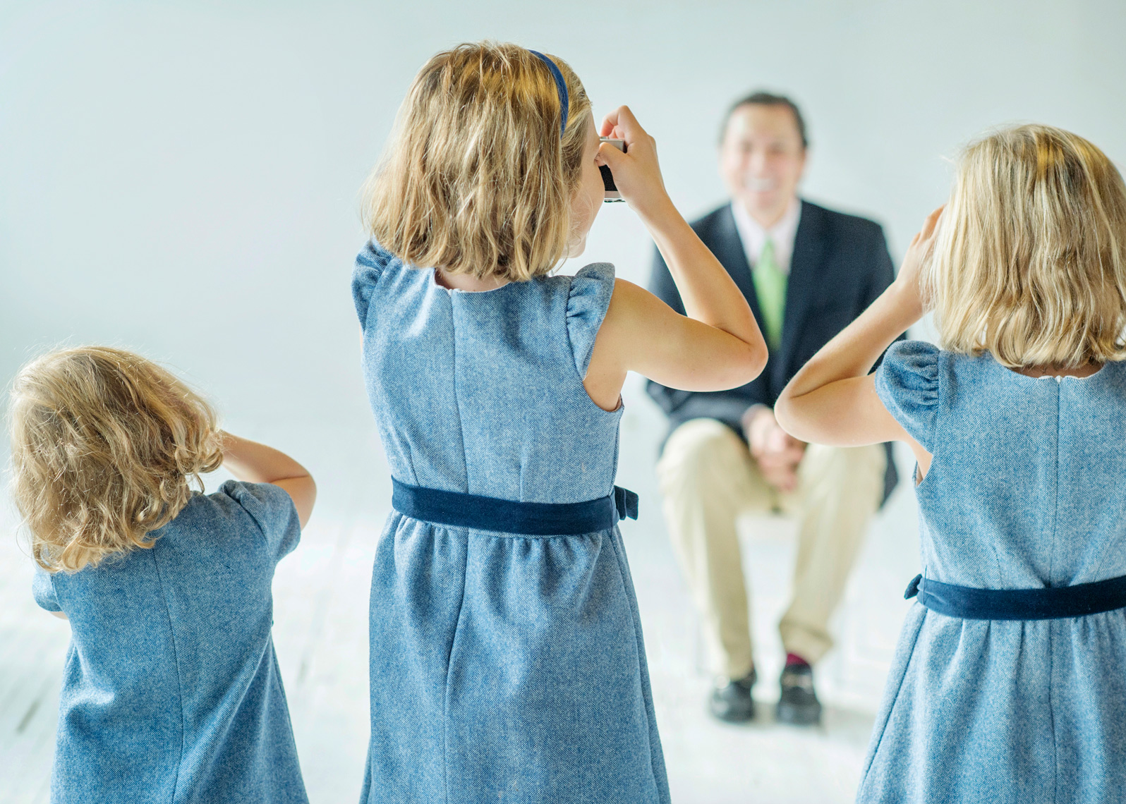 girls in matching dresses taking photo of their dad in studio
