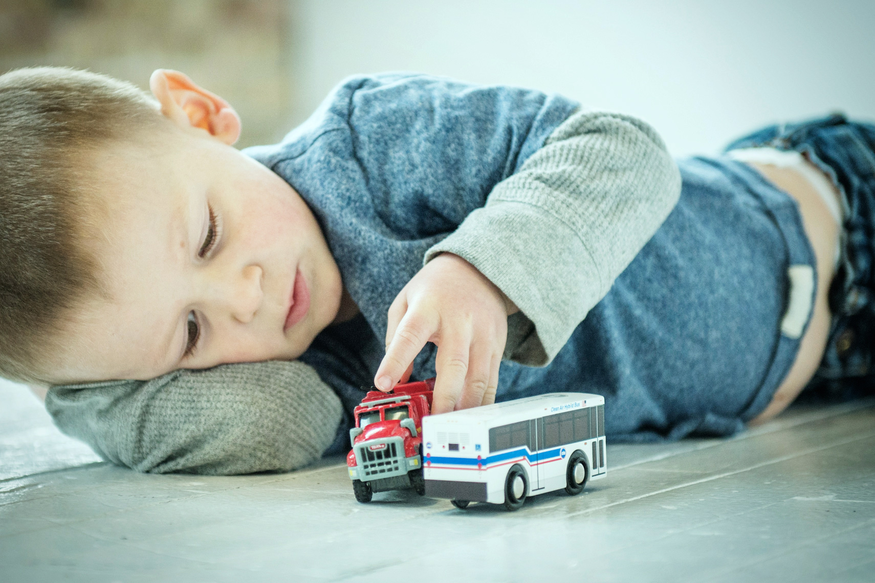 boy playing with toy bus lifestyle photography