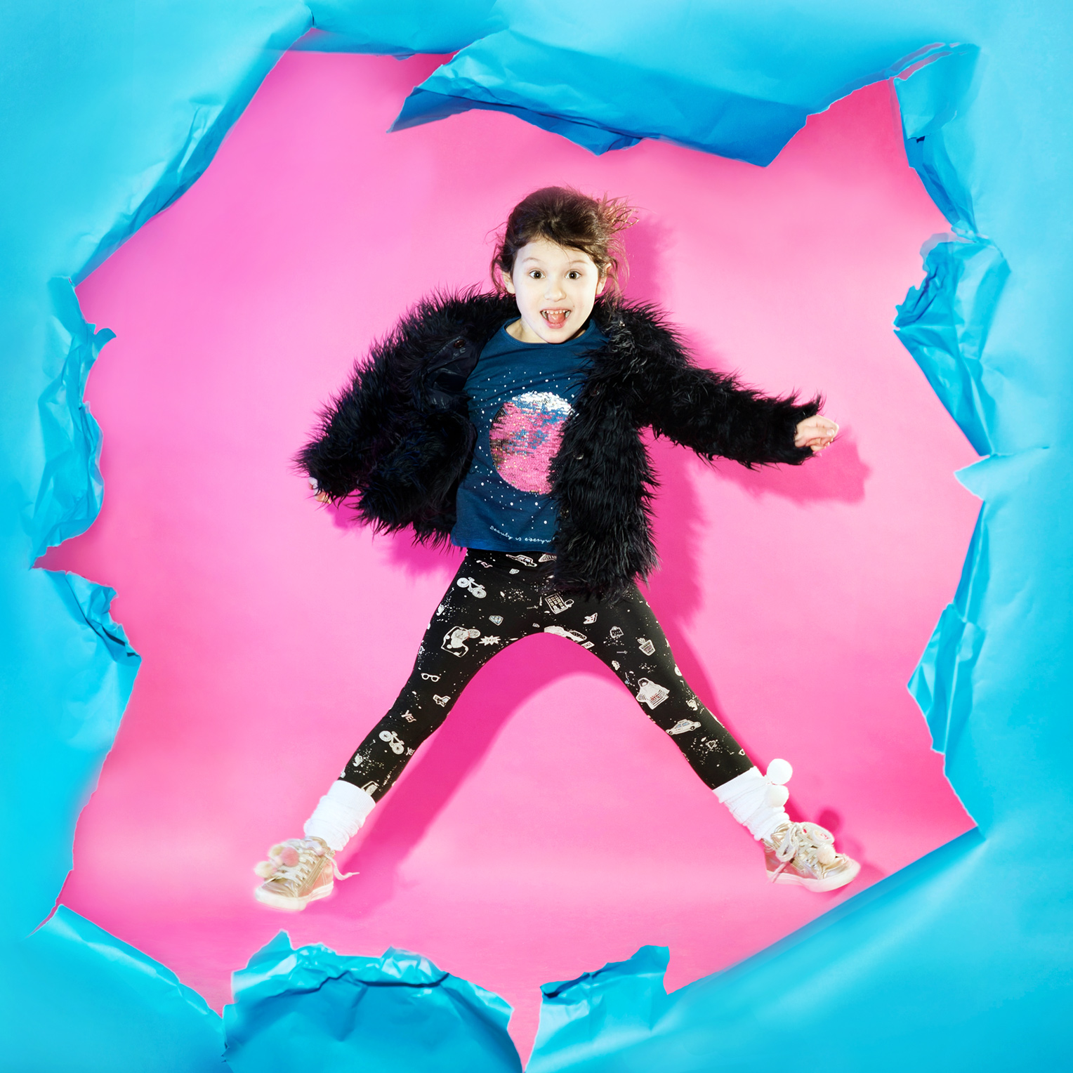 girl jumping in pink and blue studio