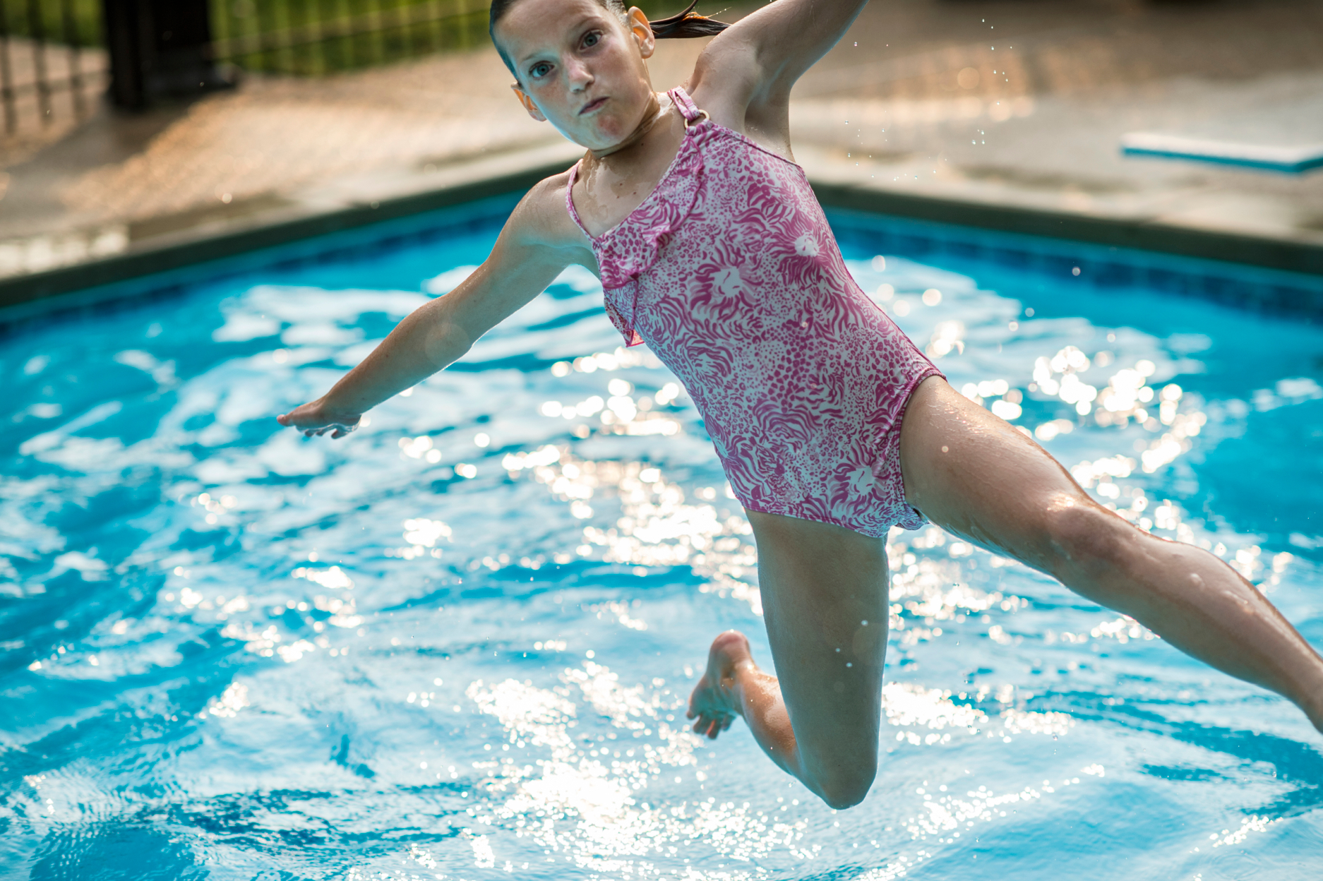 girl jumping in pool with pink bathing suit