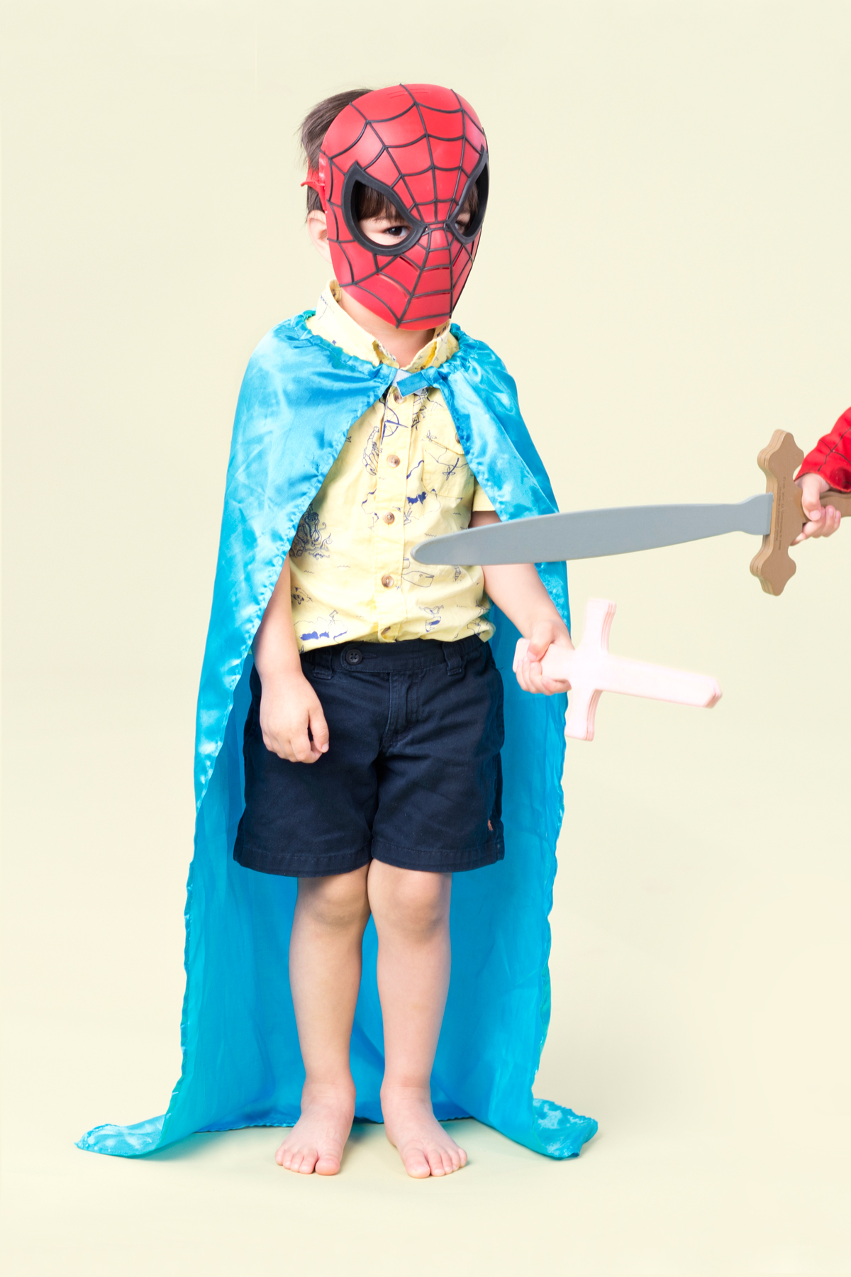 boy in spiderman mask with cape and sword