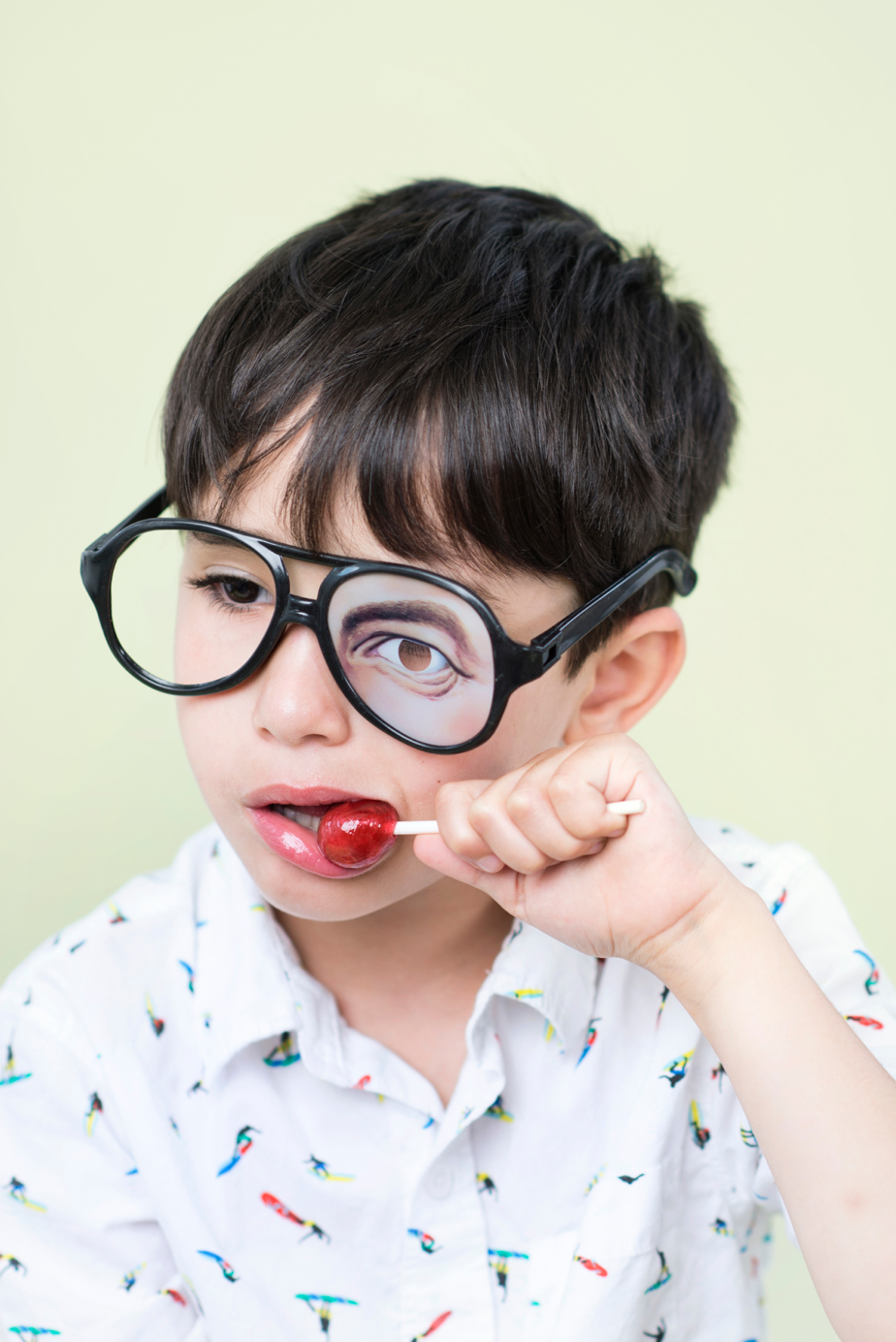 boy with silly glasses eating lollipop