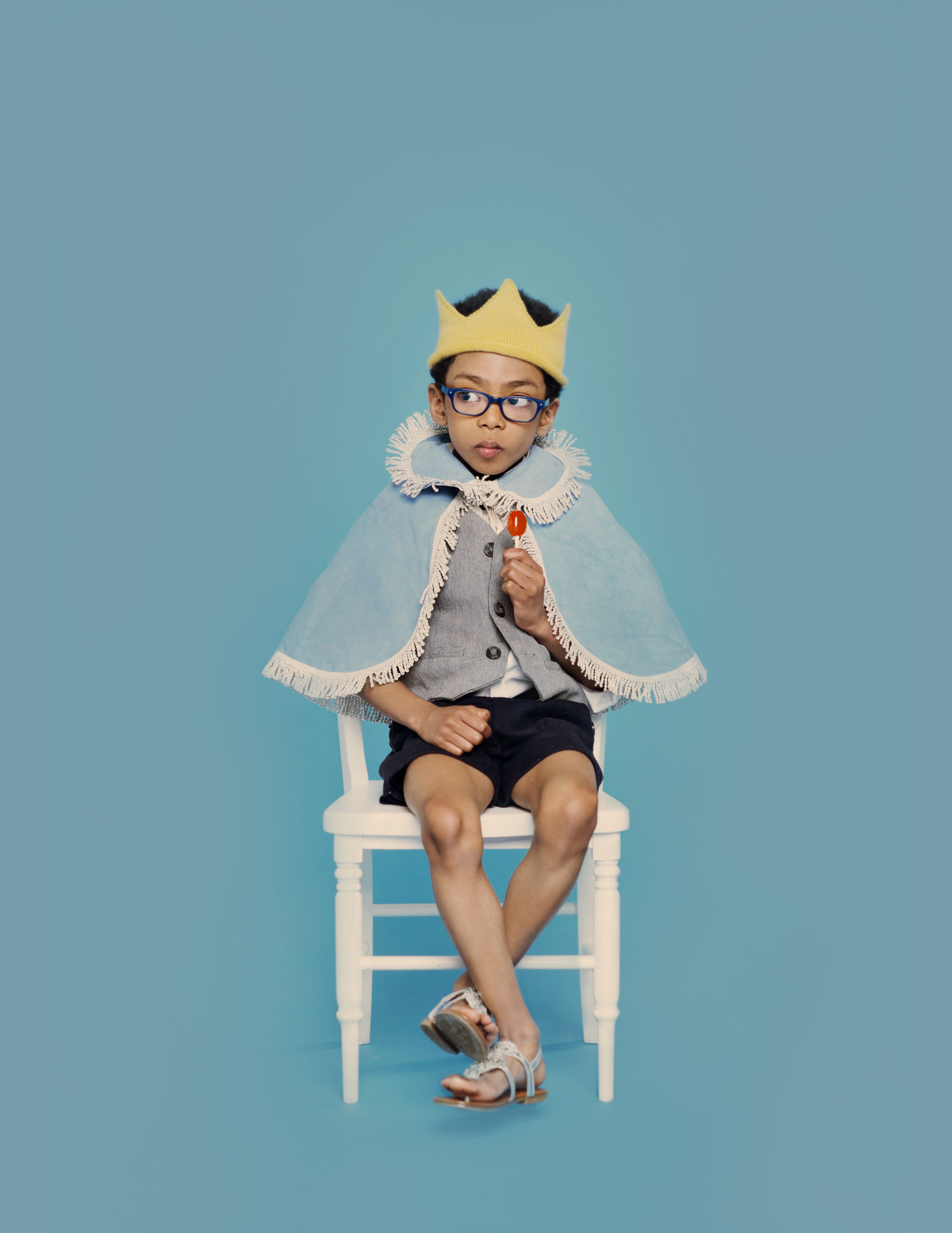 boy dressed as the little prince in blue cape with lollipop