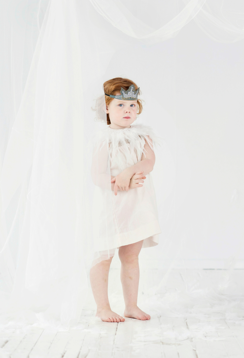 girl in white feather costume with crown