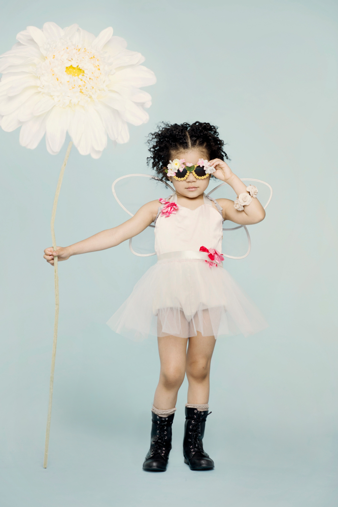 girl with giant flower and boots and sunglasses