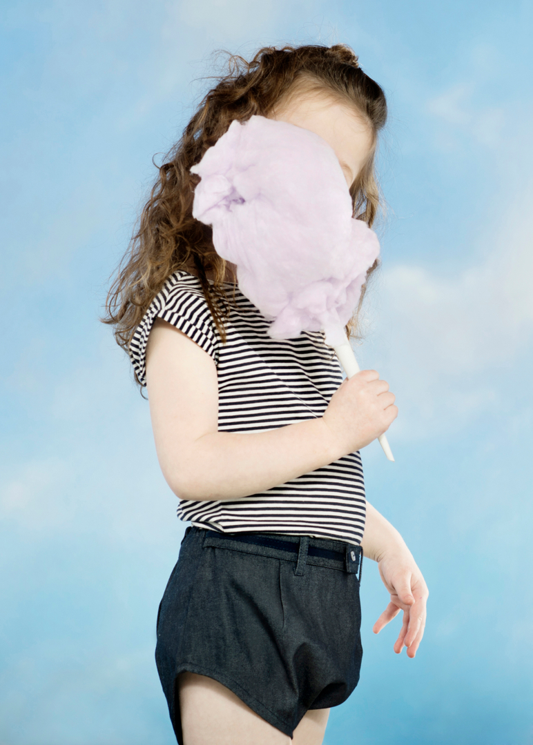 girl eating cotton candy with face obscured