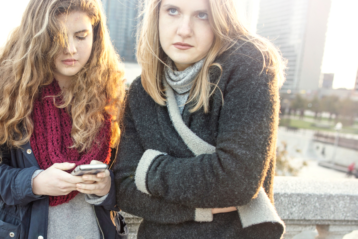 grumpy sisters in sweaters with cell phone