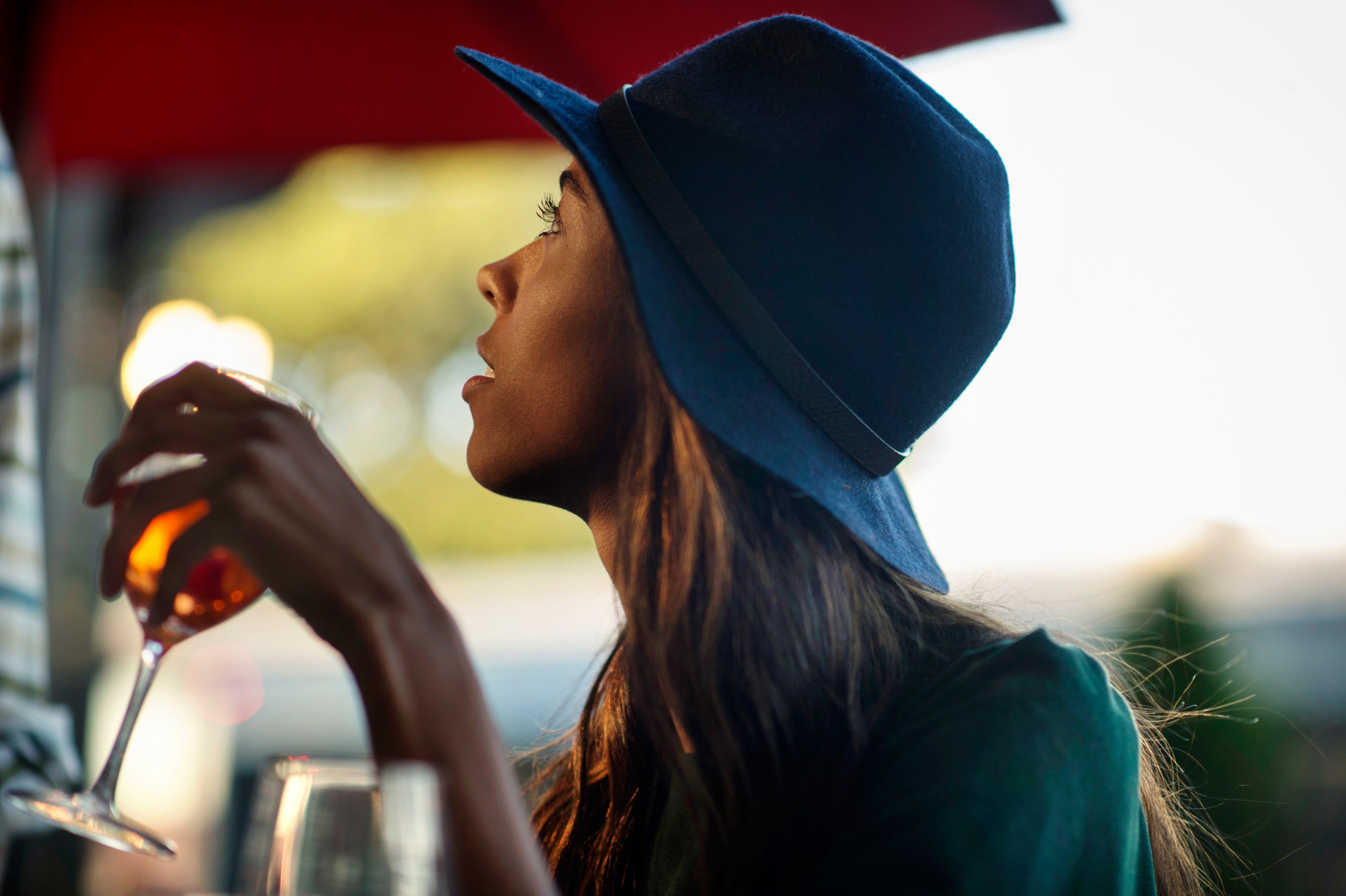 girl in silhouette drinking wine with blue fedora